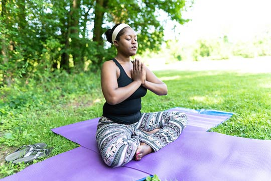 Woman Meditating at Yoga in the Parks
