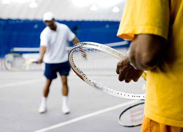 A close up of a man holding a tennis racket with a tennis teacher in the background