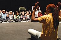 Performer sitting in front of children