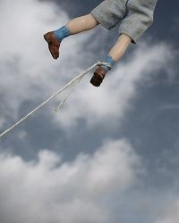 child flying away in the sky but still tethered to the ground with a rope by his legs