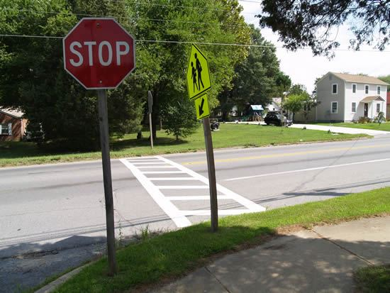 Stop sign and crosswalk sign on the side of a road by sidewalk